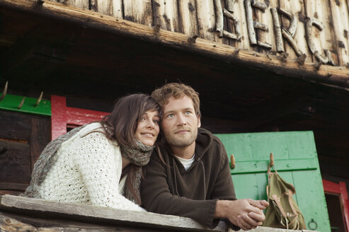 Young couple leaning on wooden rail in front of alpine hut - BABF00075