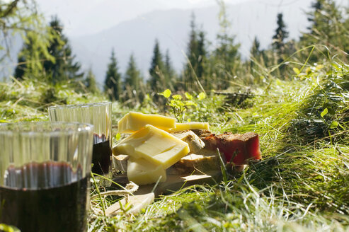 Bread, cheese and ham by glasses with red wine in meadow - BABF00069
