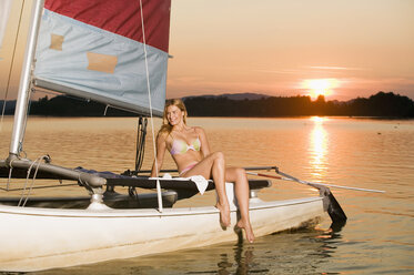 Woman sitting on sailing boat at sunset - ABF00114