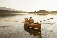 Young woman sitting on rowing boat in lake - ABF00108