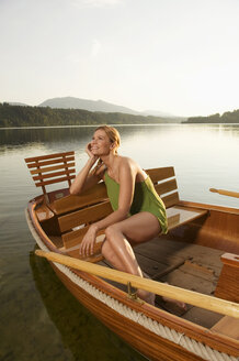 Young woman sitting on rowing boat in lake - ABF00105