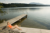 Woman relaxing on jetty - ABF00084
