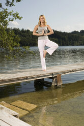 Woman exercising yoga on jetty - ABF00081