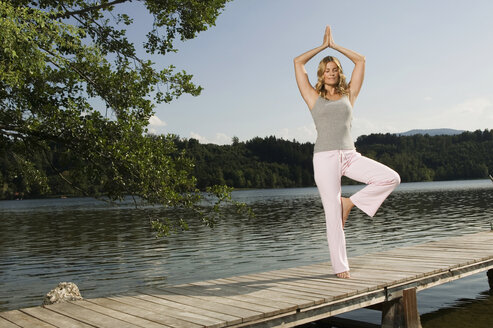 Woman exercising yoga on jetty - ABF00078