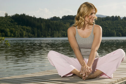 Woman exercising yoga on jetty - ABF00075