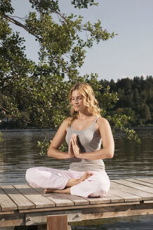 Woman exercising yoga on jetty - ABF00072