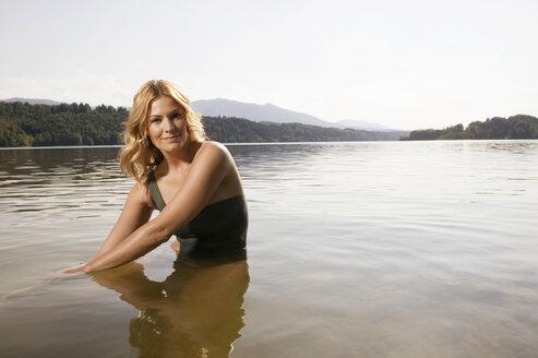 Woman sitting in lake, portrait - ABF00066