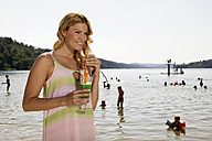 Woman holding cocktail at lake, smiling - ABF00063