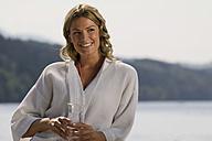 Woman wearing bathrobe, holding glass of water - ABF00060