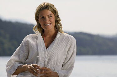 Woman wearing bathrobe, holding glass of water - ABF00060