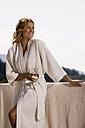 Woman wearing bathrobe, holding glass of water - ABF00057