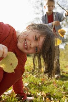 Girl (6-9) holding leaf boy (10-13) in background - RDF00181