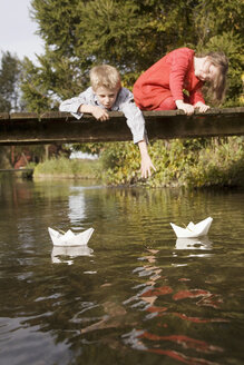 Boy (10-12) and girl (7-9) on bridge watching paper boats in water - RDF00169