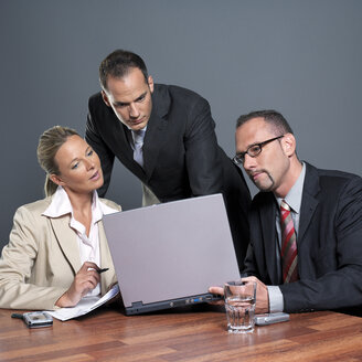Business people looking at laptop at conference table - JLF00244