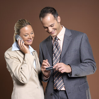 Businessman and businesswoman using mobile phone - JLF00238