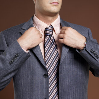 Businessman wearing suit and tie, close-up - JLF00232