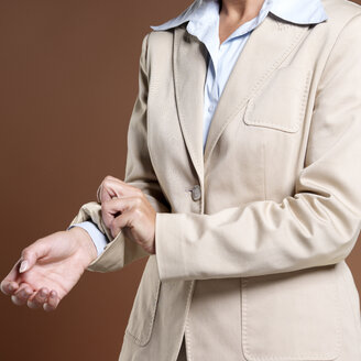 Businesswoman, close-up, rolling up sleeves - JLF00223