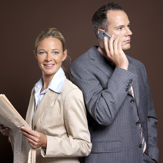 Businessman and businesswoman man using mobile phone, woman holding newspaper - JLF00220