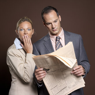 Businessman and businesswoman with newspaper, woman covering mouth - JLF00208