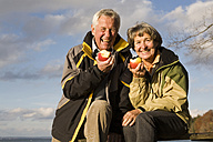 Senior couple eating apple, smiling, portrait - WESTF03529