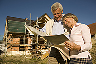 Senior couple looking at blueprints in front of incomplete built house, smiling - WESTF03457