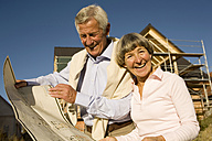 Senior couple holding plan in front of partially built house - WESTF03454
