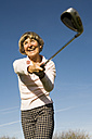 Germany, Bavaria, Ammersee, Senior woman swinging golf club, smiling, low angle view - WESTF03445