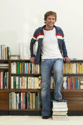 Young man standing in front of bookshelf, feet on books, portrait - WESTF03614