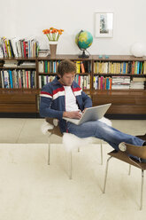 Young man sitting on chair, using laptop - WESTF03608