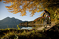 Young man mountain biking in forest - MRF00801