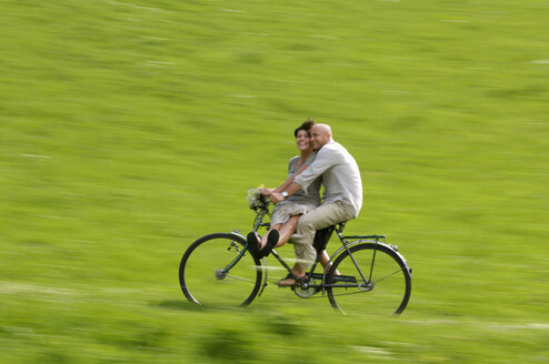 Couple riding bicycle in meadow - HHF00899