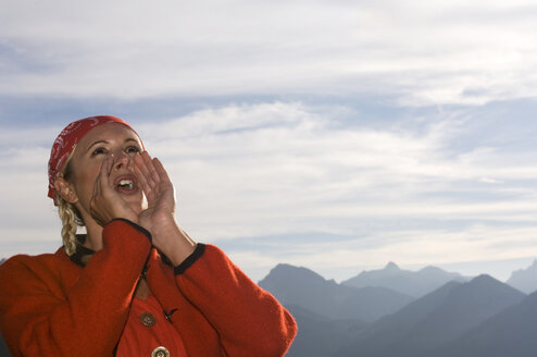 Young woman in mountains shouting, low angle view, portrait - HHF00977