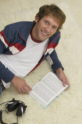 Young man lying on floor, reading book - WESTF03682