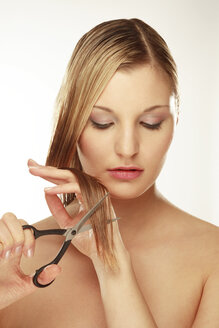 Young woman holding scissors and cutting hair, close-up - LDF00448
