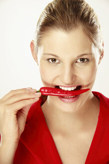 Young woman holding chilies between teeth, close-up, portrait - LDF00436