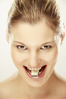 Young woman with candy between teeth - LDF00433
