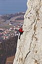 Germany, Bavaria, man climbing on rock face, side view - FFF00743