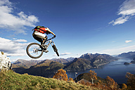Italy, Lake Como, man performing jump on bicycle - FFF00721