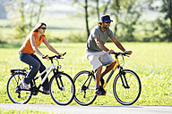 Germany, Bavaria, couple riding bicycle, side view - FFF00708