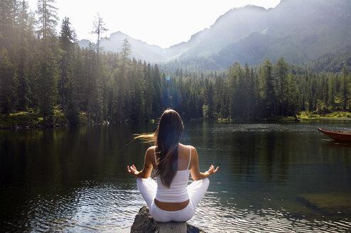 Woman exercising yoga at lake, rear view - HHF01147