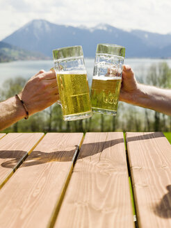 Germany, Bavarian, Tegernsee, two men toasting with beer glasses, close-up - KMF00685
