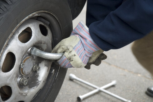 Man changing tire, close-up - NHF00296
