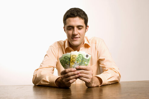 Young man holding diverified Euro banknotes - LDF00466