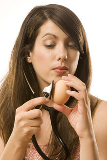 Young woman holding stethoscope on egg - CLF00318