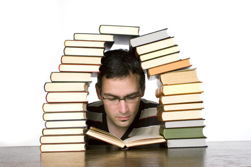 Young man reading by piled books, close-up - CLF00300