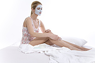 Woman with beauty mask on face, sitting on bed - MAEF00249