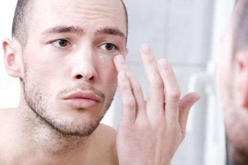 Man applying face cream, close-up - MAEF00171