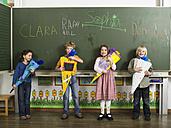 Children (4-7) standing in front of blackboard holding school cones - WESTF04592
