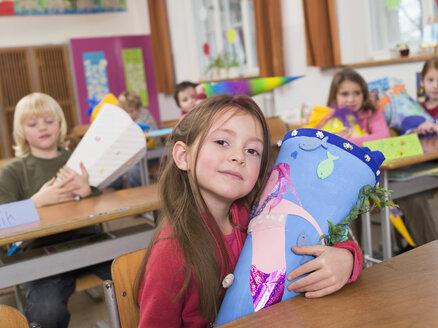 Children (4-7) in class room, holding school cones - WESTF04571