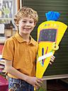 Boy (6-7) holding school cone, smiling, portrait - WESTF04476